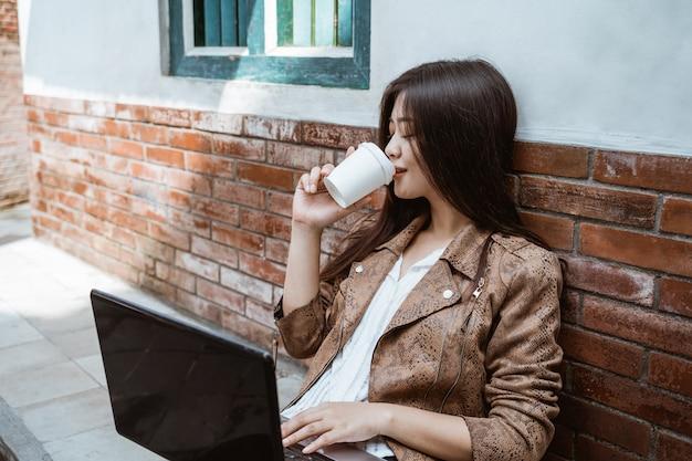 Женщина сидит и наслаждаясь кофе во время работы на открытом воздухе