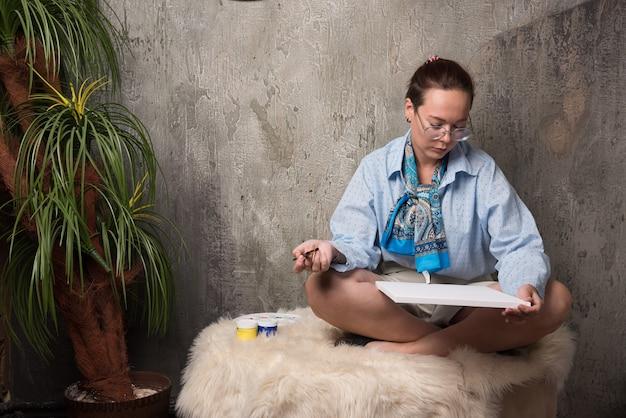 座って、大理石の背景にブラシでキャンバスを見て女性