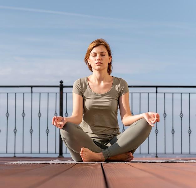Женщина сидит и медитирует на открытом воздухе