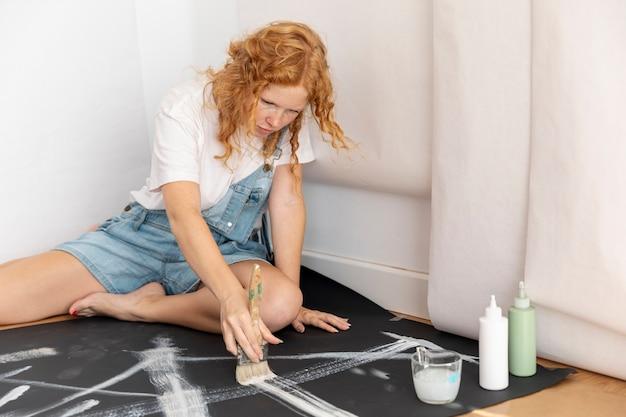 Женщина сидит и рисует кистью