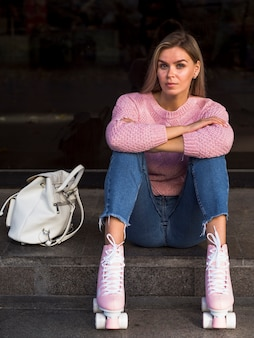 女性が座っているとバックパックでローラースケートでポーズ