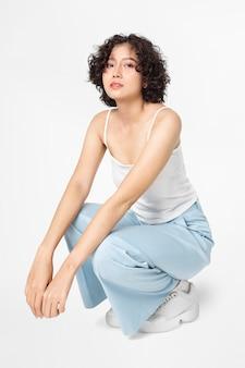 Женщина сидит и позирует в простой одежде всего тела