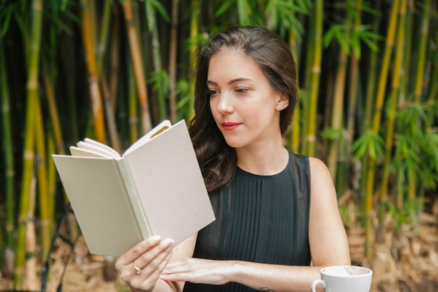 Женщина сидит и читает роман в ресторане