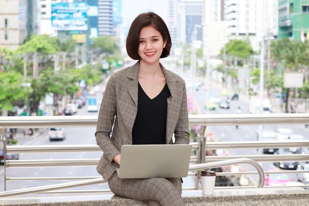 座っていると都市でコンピューターを使用している女性