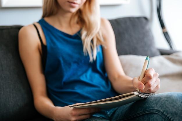 여자가 앉아서 집에서 메모장에서 작성