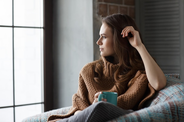 Woman sitting in an armchair with a mug of coffee looking at window