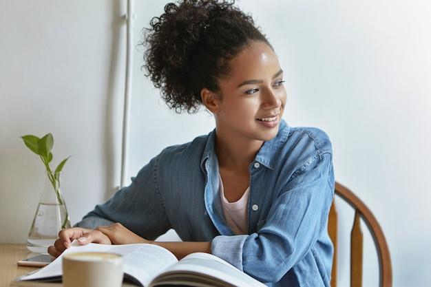 本をテーブルに座っている女性