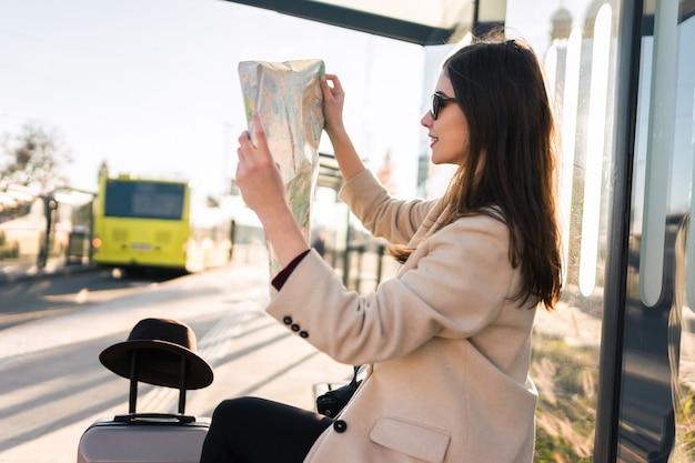 Женщина сидит на автобусной остановке и держит карту города.