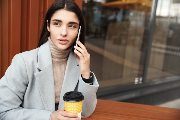 カフェに座って携帯電話で話している女性。カフェで働いている間、クライアントと話している実業家。