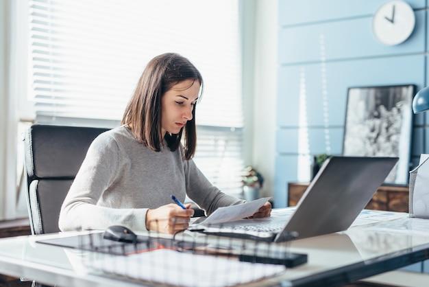 オフィスの机に座って働いている女性。
