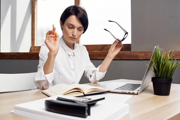 Женщина, сидящая за своим столом в офисе перед профессиональным руководителем работы ноутбука