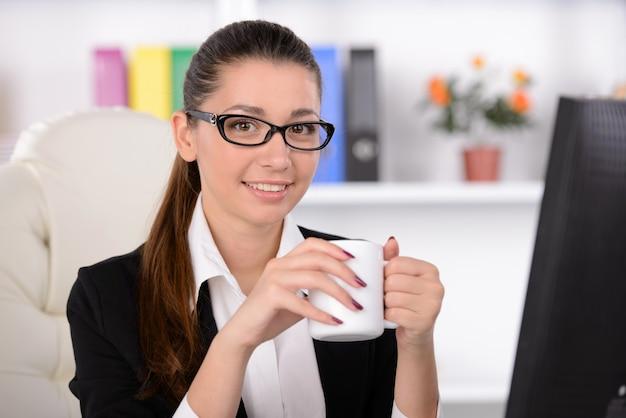彼女の職場に座っているとコーヒーを飲む女性。