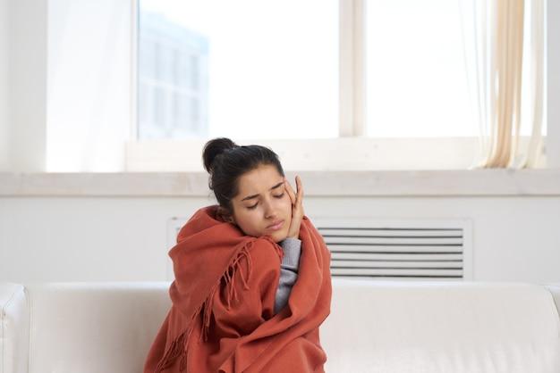 寒い毛布の健康問題で覆われた家に座っている女性。高品質の写真