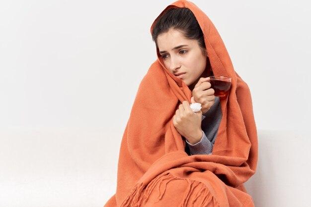 お茶の風邪治療で毛布で覆われた家に座っている女性