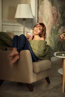 여자 니트 따뜻한 스웨터를 입고 뜨거운 커피 한잔과 함께 창가의 자에 집에 앉아. 빛이 가득한 아늑한 햇살 가득한 방. 큰 창 뒤에 아름다운 아침.