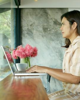 ラップトップを使用して自宅で座っている女性