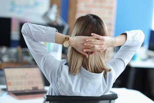 テーブルに座って、頭の後ろで彼女の手を保持している女性。成功した女性のビジネスコンセプト