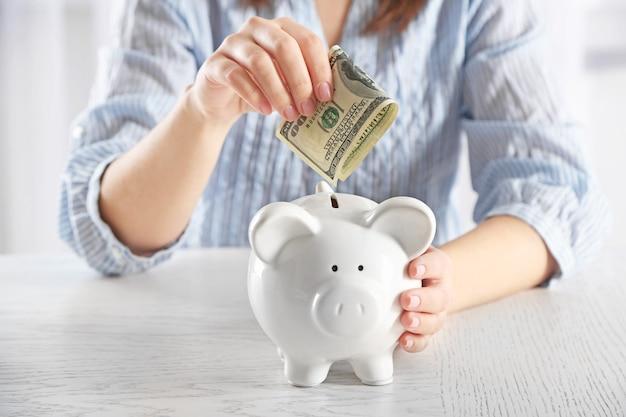 テーブルに座って貯金箱のクローズアップにお金を入れている女性