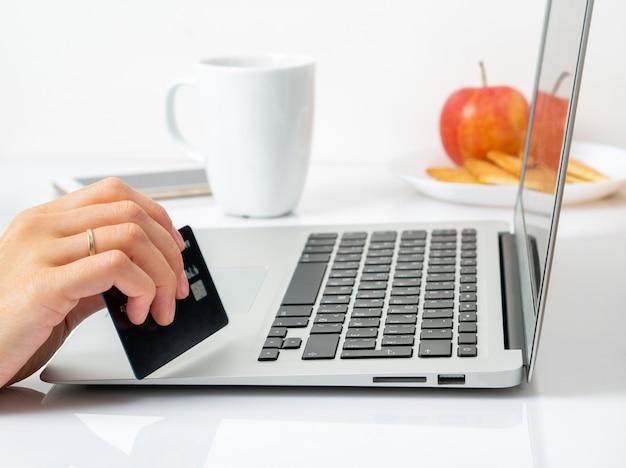 Женщина сидит за столом дома и смотрит на ноутбук, оплачивает покупки кредитной картой