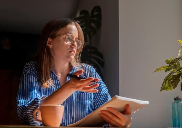 Женщина сидит за столиком в кафе и объясняет что-то бизнес-консультант