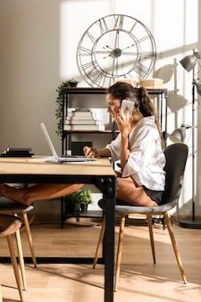 Женщина, сидящая за столом, разговаривает по телефону