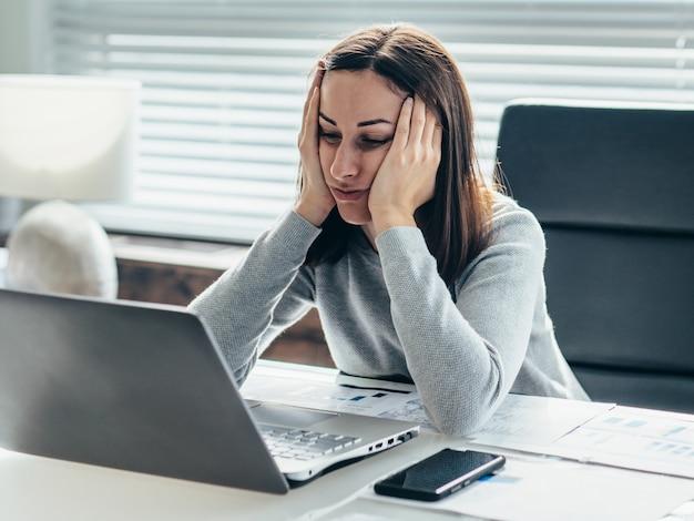頭を両手に寄りかかってテーブルに座ってノートパソコンのモニターを見ている女性。
