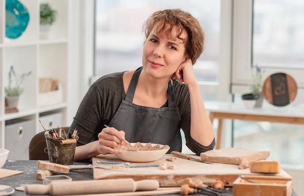 Женщина, сидящая за столом с керамикой во время работы в световой мастерской