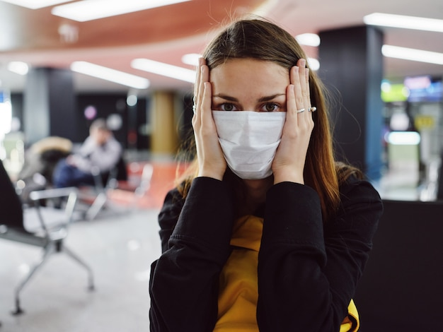 医療用マスクを着用し、フライトを待っている間彼女の顔を保持している空港に座っている女性