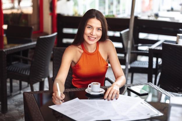 テーブルに座っている女性は、ドキュメントに署名します。一杯のコーヒーで。カフェ。幸せの広い笑顔。家の外で働きます。