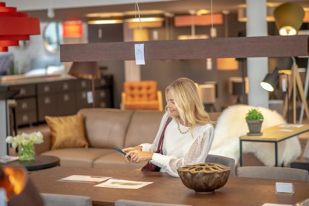 Женщина сидя на таблице принимая фото листов бумаги на smartphone в мебельном магазине, счастливая.