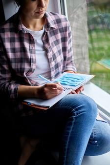 窓際に座っている女性、ノートブック計画を書いている、検疫終了後のリストを行う、コロノウイルスが終了