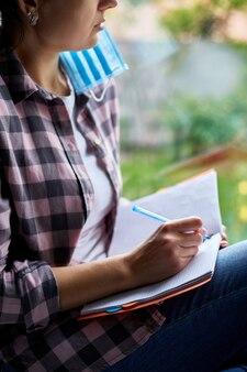여자는 창에 앉아 노트북 계획 작성, 목록