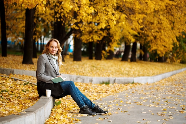 Woman sitting in autumn city park with golden treeswriting something in her notebook
