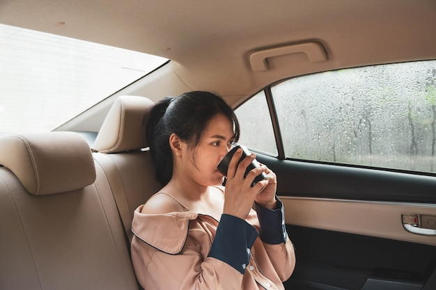 A woman sitting in the back of a car drinking coffee in a lonely mood