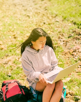Woman sitting on backpack and working in laptop