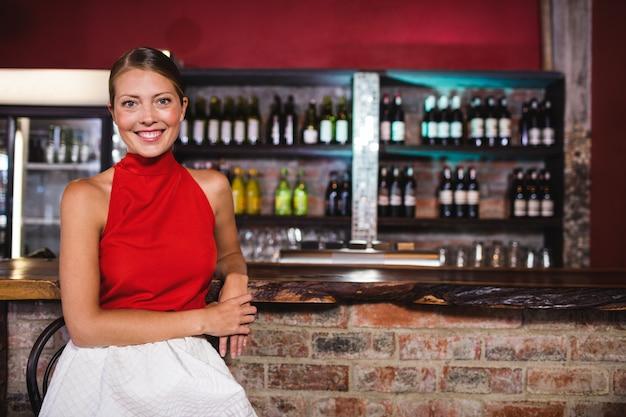 Woman sitting at bar counter in bar