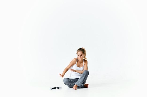 手で床のダンベルに裸足で座っている女性は、筋肉のトレーニングを行使します