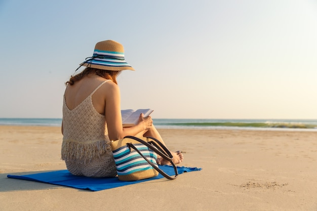 Woman sitting on beach and reading book