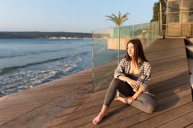 Donna seduta vicino alla spiaggia con copia spazio