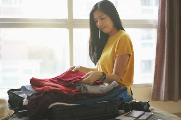 Woman sitting on bed and pack clothes in suitcase bag in bedroom