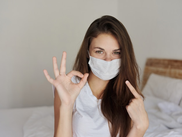 Woman sitting on bed showing finger to mask positive hand gesture