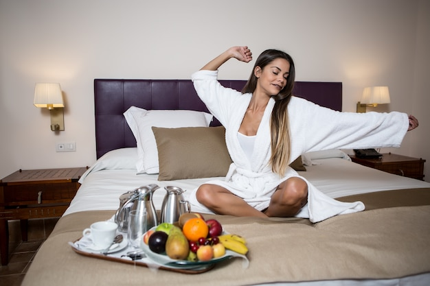 Woman sitting on bed and stretching