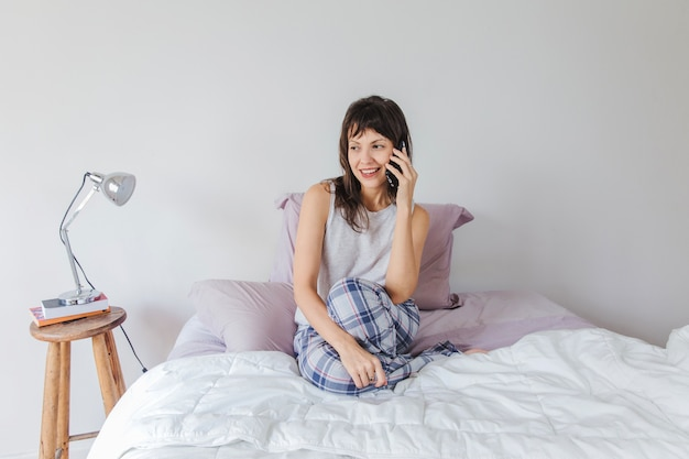 Woman sitting on bed talking on the phone