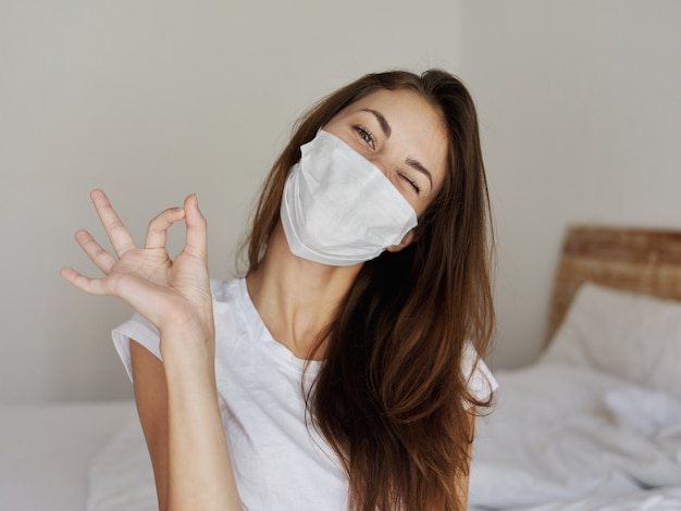 Woman sitting on bed wearing medical mask positive gesture hand emotion