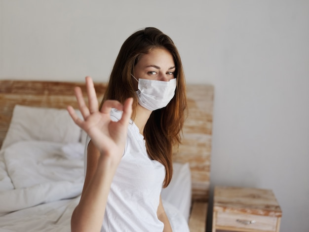 Woman sitting on bed wearing medical mask positive hand gesture