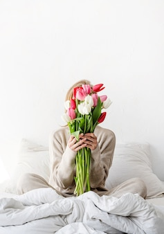 Woman sitting on the bed wearing pajamas holding tulip flowers bouquet in front of her face