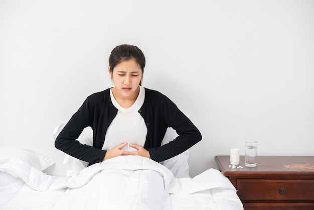 A woman sitting in bed with abdominal pain and pressing her hand on her stomach.
