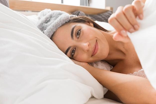 Donna seduta a letto con la testa sul cuscino