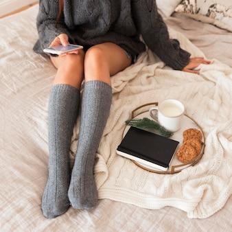 Donna seduta sul letto con latte, biscotti e agenda