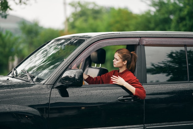 車の旅行旅行の自然のハンドルの後ろに座っている女性